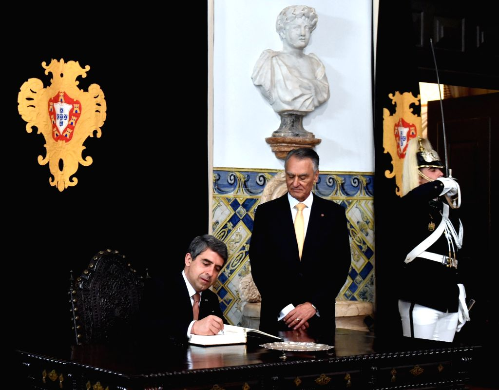 Portuguese President Anibal Cavaco Silva (R) watches his Bulgarian counterpart Rosen Plevneliev signing the honor book at the Belem Palace, in Lisbon, Portugal, on ...