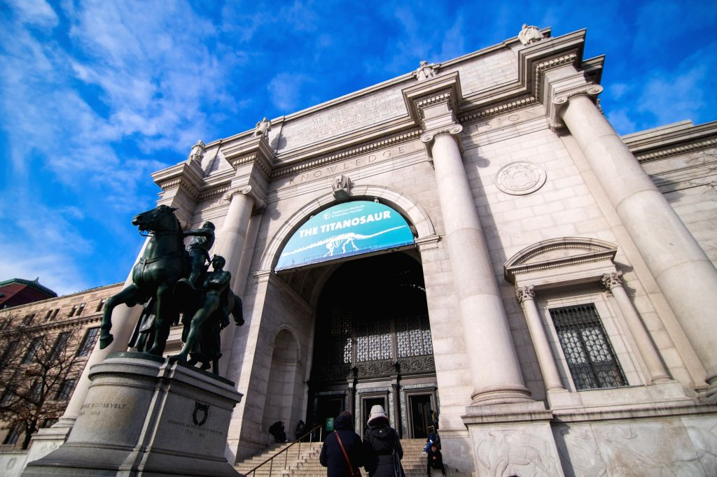 "Poster of the ""Titanosaur"" skeleton exibition is seen on the facade of the American Museum of Natural History in New York, the United States, on Jan. 14, ..."