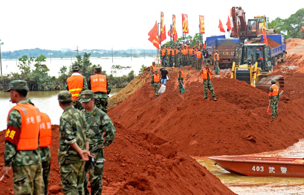 POYANG, June 24, 2016 - Soldiers work to mend a breach on the Xiangyang Dyke in Guxiandu Township of Poyang County, east China's Jiangxi Province, June 24, 2016. After days of heavy rain, a river in ...