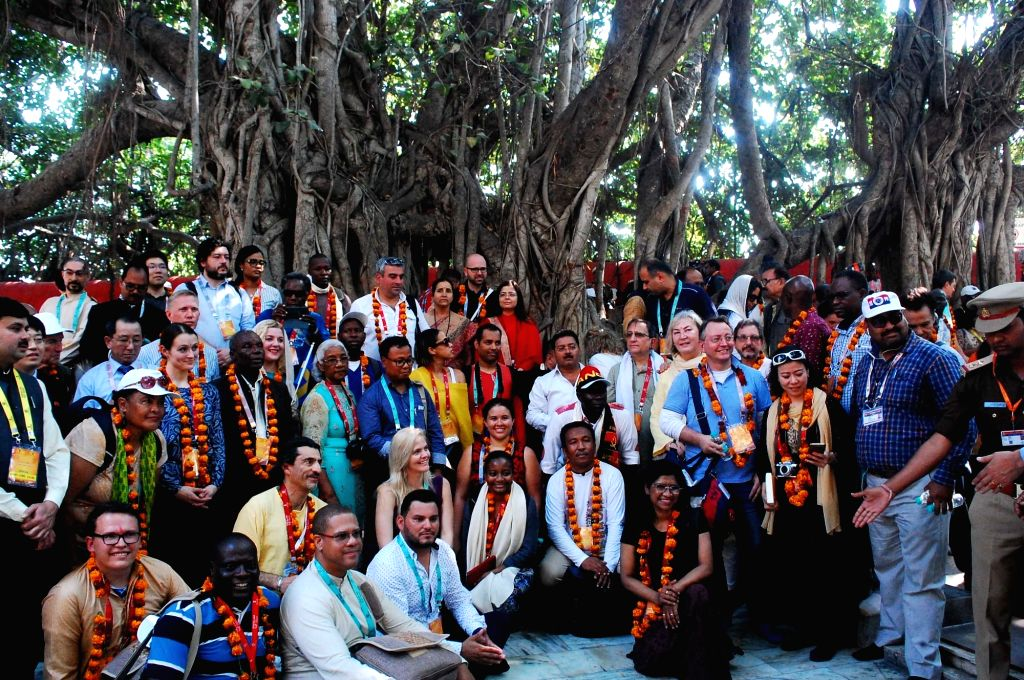 Prayagraj: Foreign delegates during the visit to the ongoing Kumbh mela in Prayagraj on Feb 22, 2019. Two hundred and twenty delegates from 185 countries across the world landed in the city to take part in the festival. These visitors are part of a d - K. Singh