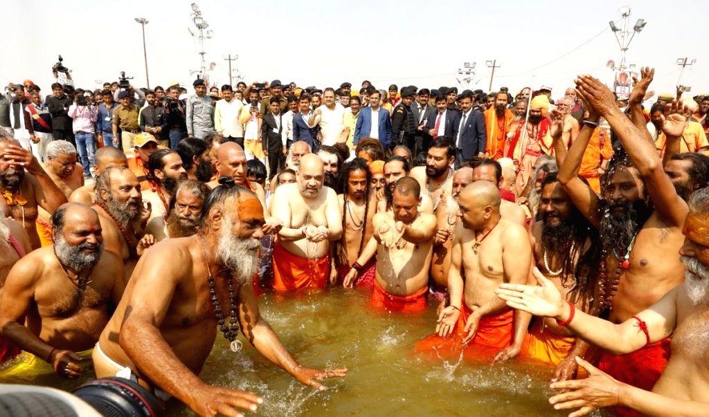 Prayagraj: Uttar Pradesh Chief Minister Yogi Adityanath and BJP chief Amit Shah take a holy dip at Sangam - the trinity of rivers Ganga, Yamuna and the mythical Saraswati -  during Kumbh Mela 2019, in Prayagraj, on Feb 13, 2019. (Photo: @AmitShah/Twi - Yogi Adityanath and Amit Shah