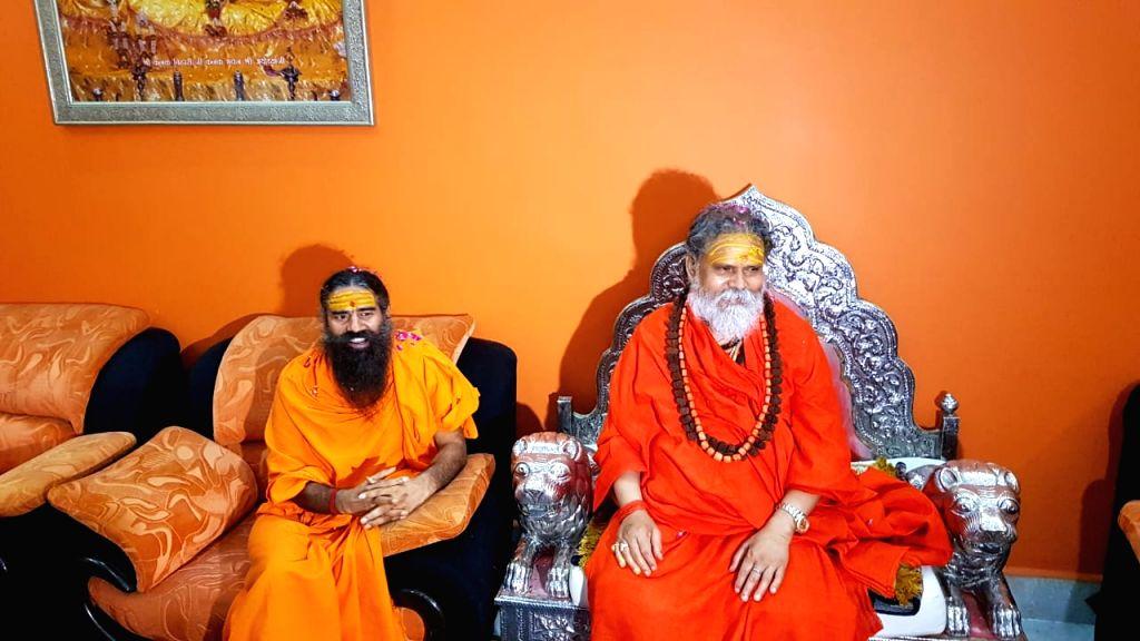 Prayagraj: Yoga Guru Baba Ramdev meets Akhil Bharatiya Akhara Parishad (ABAP) president Mahant Narendra Giri at Math Bagambari Gaddi in Prayagraj on Aug 7, 2019. (Photo: IANS)