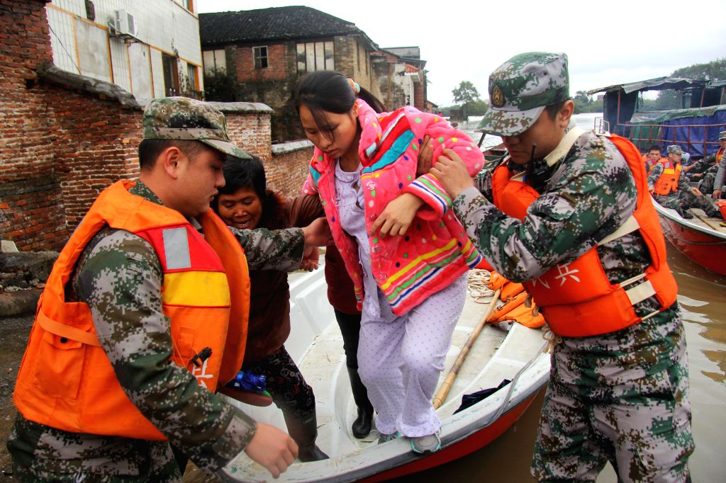 Pregnant villager Lu Caihong is transferred to a hospital by rescuers on a boat as she is trapped by flood in Daoxian County of Yongzhou City, central China's ...