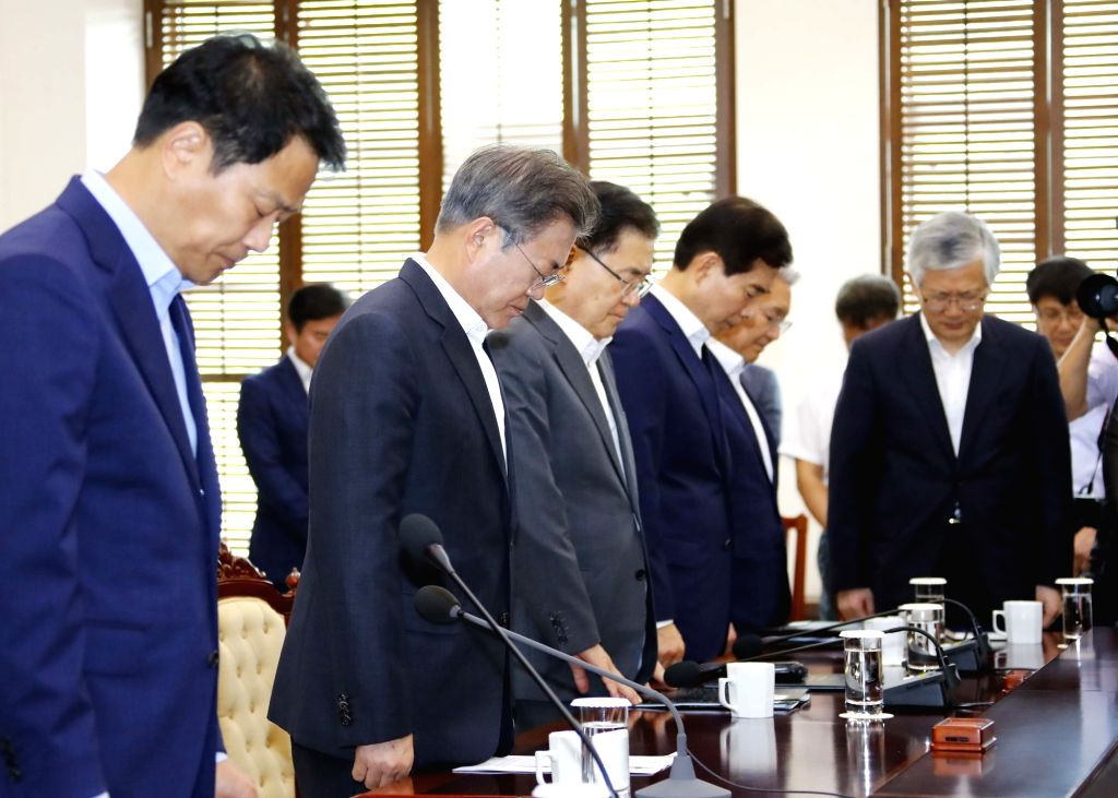 President Moon Jae-in (2nd from L) and his senior secretaries offer a silent prayer during their meeting at the presidential office Cheong Wa Dae in Seoul on July 23, 2018. They paid tribute ...