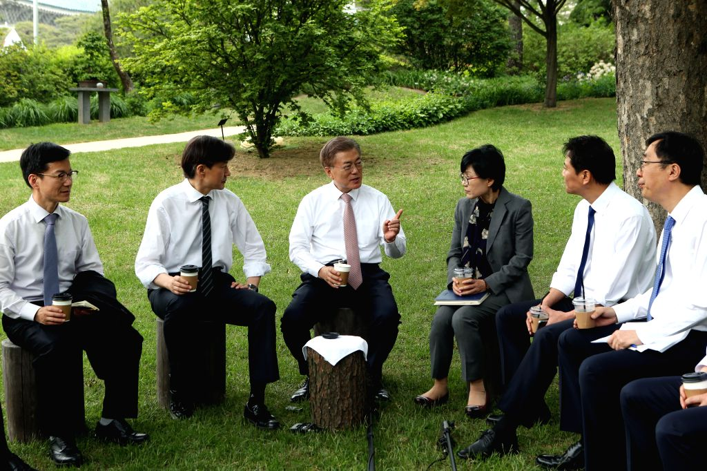 President Moon Jae-in (3rd from L) has a tea meeting with his senior presidential secretaries at a Cheong Wa Dae park in Seoul on May 11, 2017.