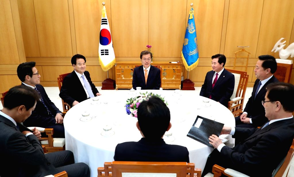 President Moon Jae-in (C) meets with a group of ruling and opposition party lawmakers at the presidential office Cheong Wa Dae on Oct. 11, 2017, in this photo provided by the office. The legislators ...