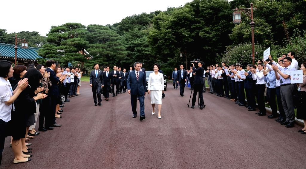 President Moon Jae-in (L) and first lady Kim Jung-sook are sent off by employees of the presidential office Cheong Wa Dae in Seoul on Sept. 18, 2018, as they head to an airport to fly to ...