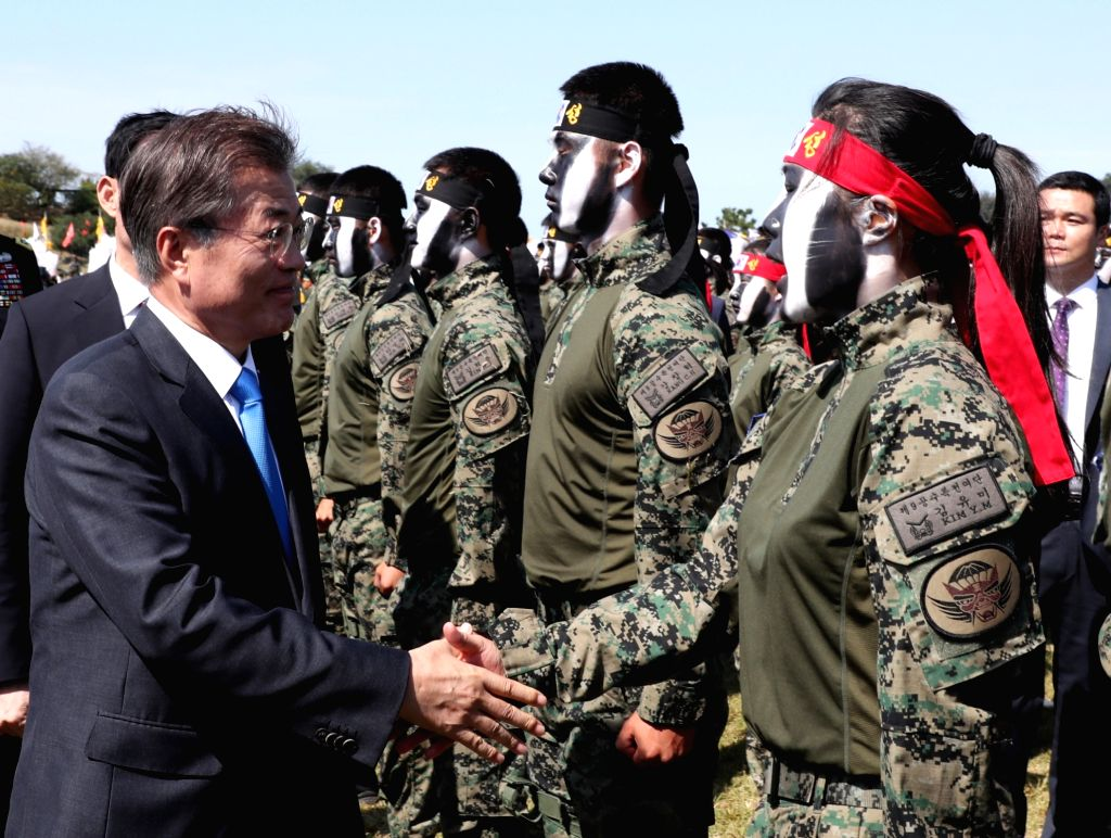 President Moon Jae-in (L) shakes hands with Kim Yu-mi, a member of the Army's Special Warfare Command, during a ceremony at the Korean Navy 2nd Fleet in Pyeongtaek, 70 kilometers southwest of ...