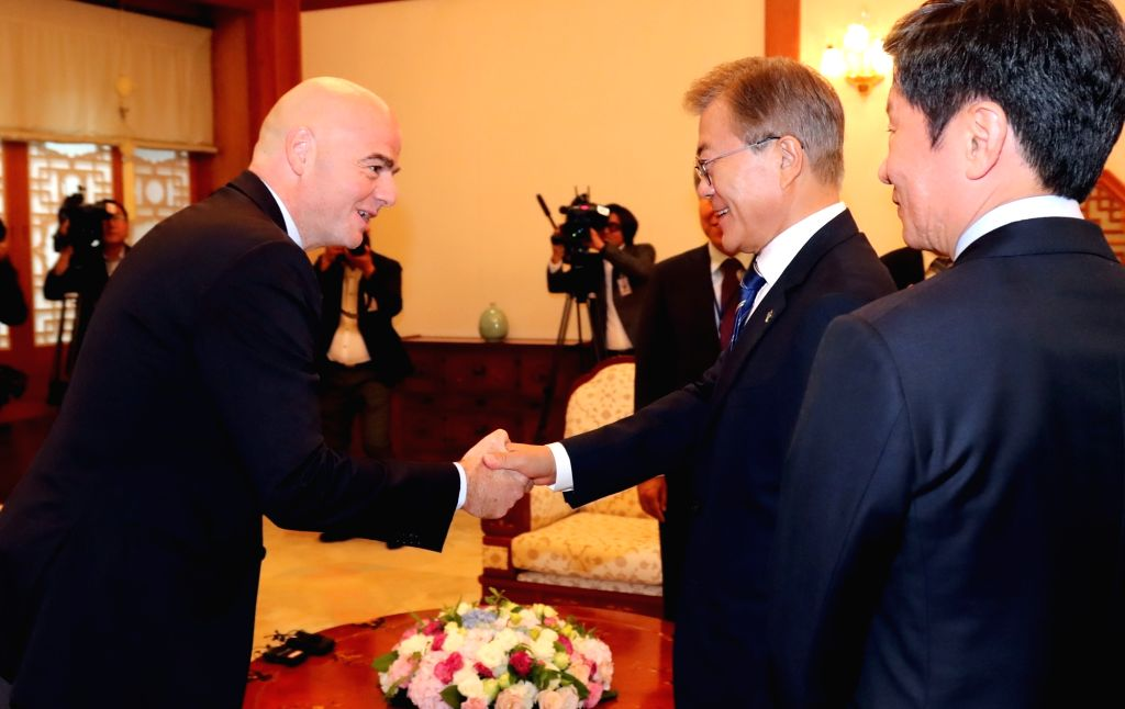 President Moon Jae-in (R) shakes hands with visiting FIFA President Gianni Infantino at the presidential office Cheong Wa Dae in Seoul on June 12, 2017.