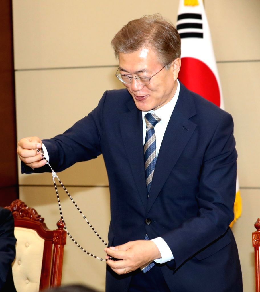 President Moon Jae-in takes a look at a rosary after Kim Hee-joong (not pictured), archbishop of the Catholic Bishops' Conference of Korea, gave Moon the present from Pope Francis during their ...