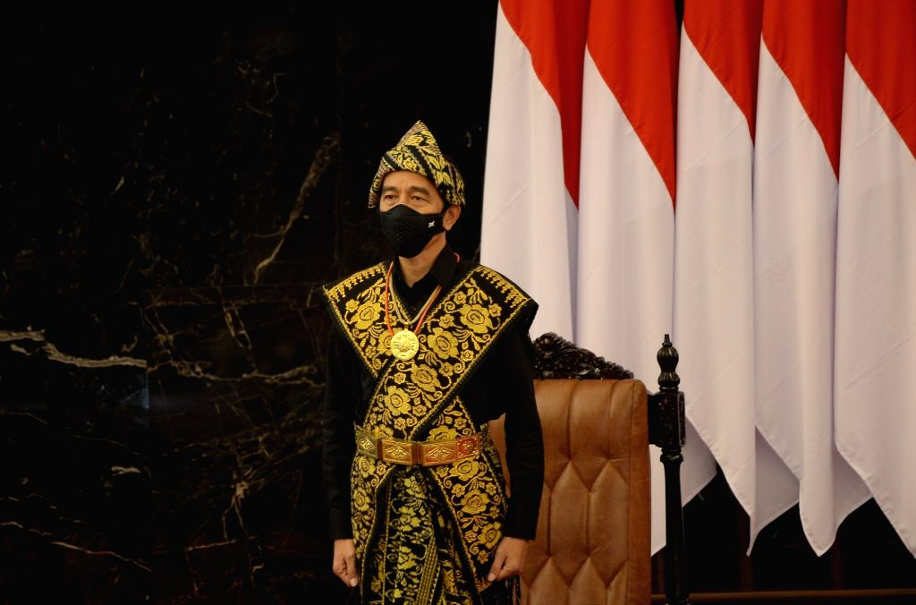 President of Indonesia Joko Widodo, wearing a face mask, stands up to deliver his annual speech in front of members of the parliament at the parliament building in ...