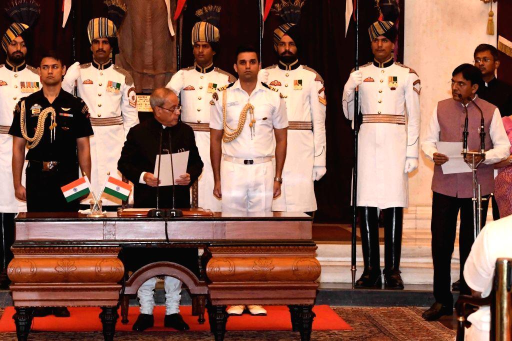 President Pranab Mukherjee administers the oath of Minister of State to Mansukh L. Mandaviya, at a swearing-in ceremony organised at Rashtrapati Bhavan, in New Delhi on July 5, 2016. - Pranab Mukherjee