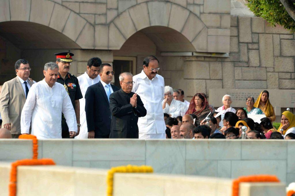 President Pranab Mukherjee, pays tribute to Mahatma Gandhi on his birth anniversary at Raj Ghat in New Delhi on Oct 2, 2016. Also seen Union Minister for Urban Development, Housing and ... - M. Venkaiah Naidu and Pranab Mukherjee