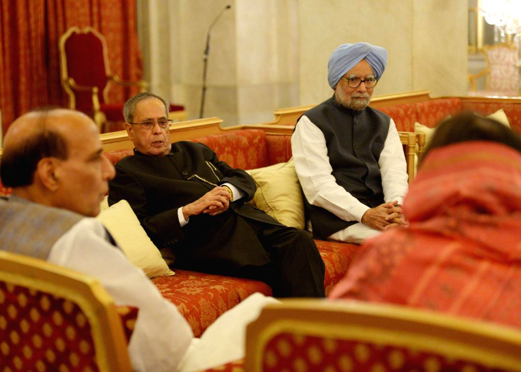 President Pranab Mukherjee with former Prime Minister Manmohan Singh and Union Home Minister Rajnath Singh during an Iftar Party at the Rashtrapati Bhawan in New Delhi on July 21, 2014. - Manmohan Singh, Pranab Mukherjee and Rajnath Singh