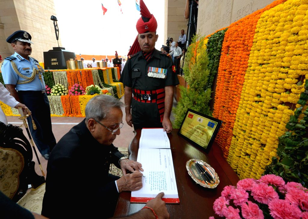 President Pranab Mukherjee writes a message at Amar Jawan Jyoti, India Gate on 68th Independence Day in New Delhi on Aug 15, 2014. Also seen Chief of Air Staff, Air Chief Marshal Arup Raha. - Pranab Mukherjee