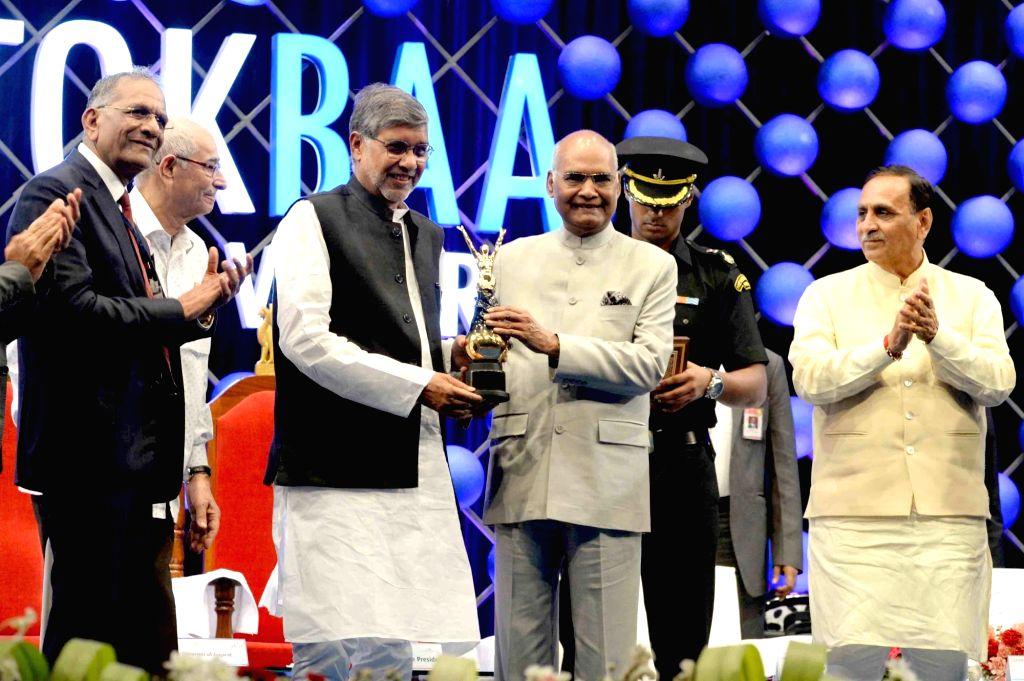 President Ram Nath Kovind presents the 'Santokbaa Humanitarian Award' to Nobel laureate Kailash Satyarthi, during the award presentation ceremony, in Surat on May 29, 2018. Also seen Gujarat ... - Vijay Rupani, Kailash Satyarthi and Nath Kovind