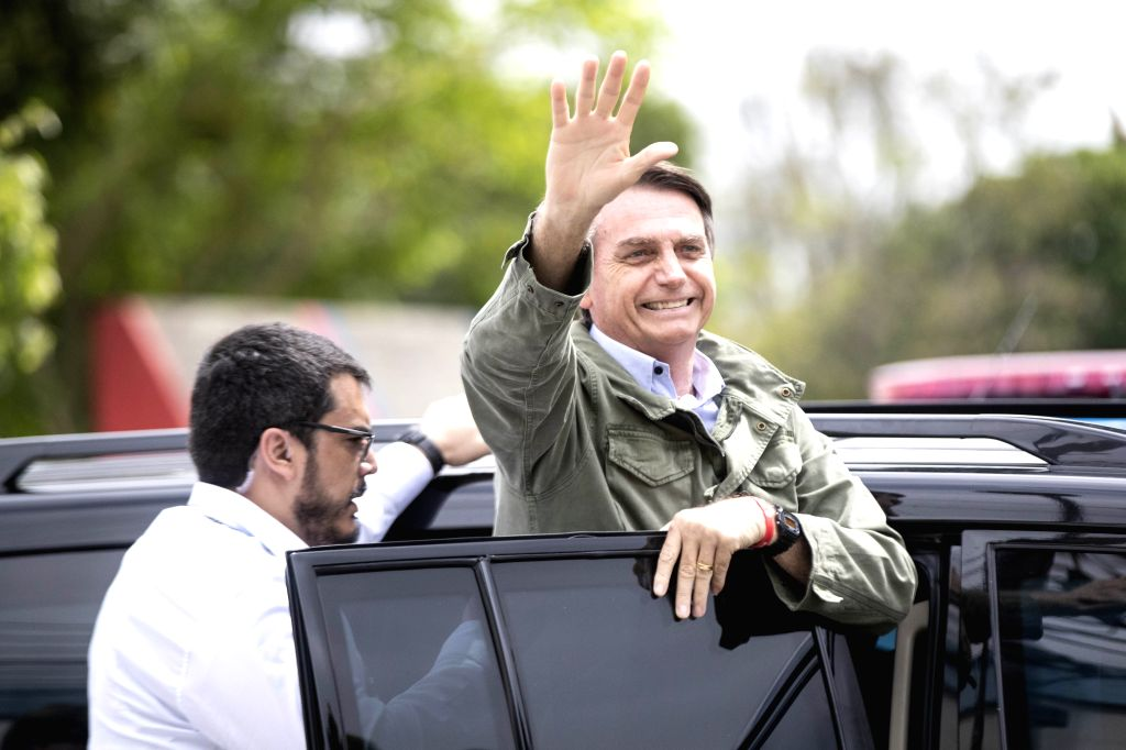 : Presidential candidate Jair Bolsonaro waves to his supporters as he leaves a polling station in Rio de Janeiro, Brazil, on Oct. 28, 2018. (Xinhua/Li ...