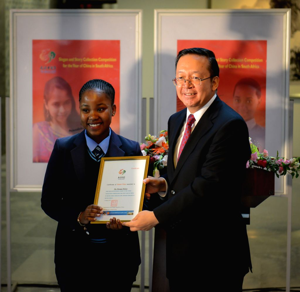 Chinese Ambassador to South Africa Tian Xuejun (R) presents an award to a winner of the slogan and story collection competition for the Year of China in South ...