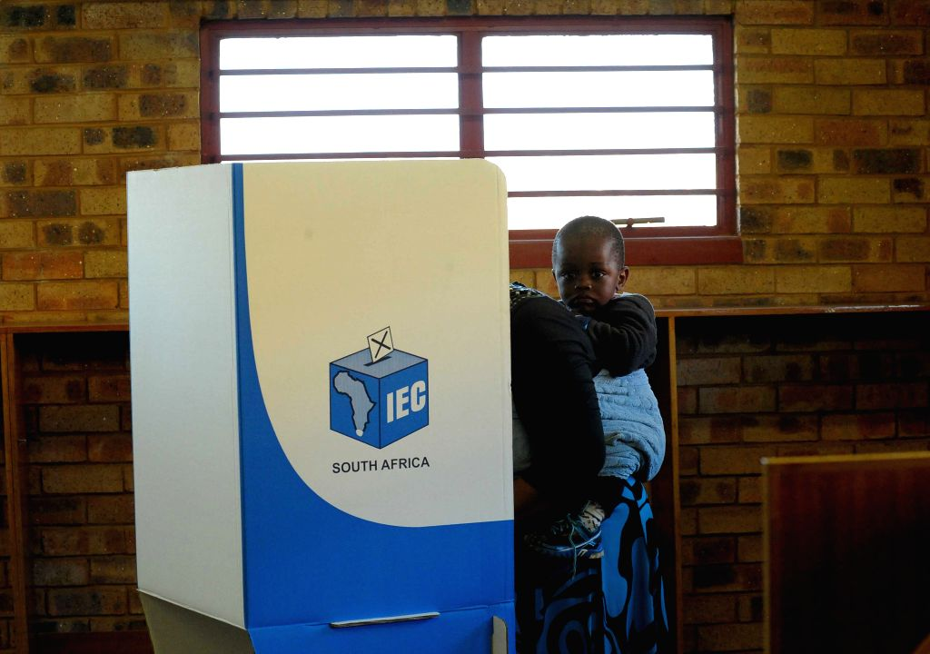 A woman carrying her child fills the ballot at a poll station in Pretoria, South Africa, May 7, 2014. South Africa on Wednesday kicked off its general election which
