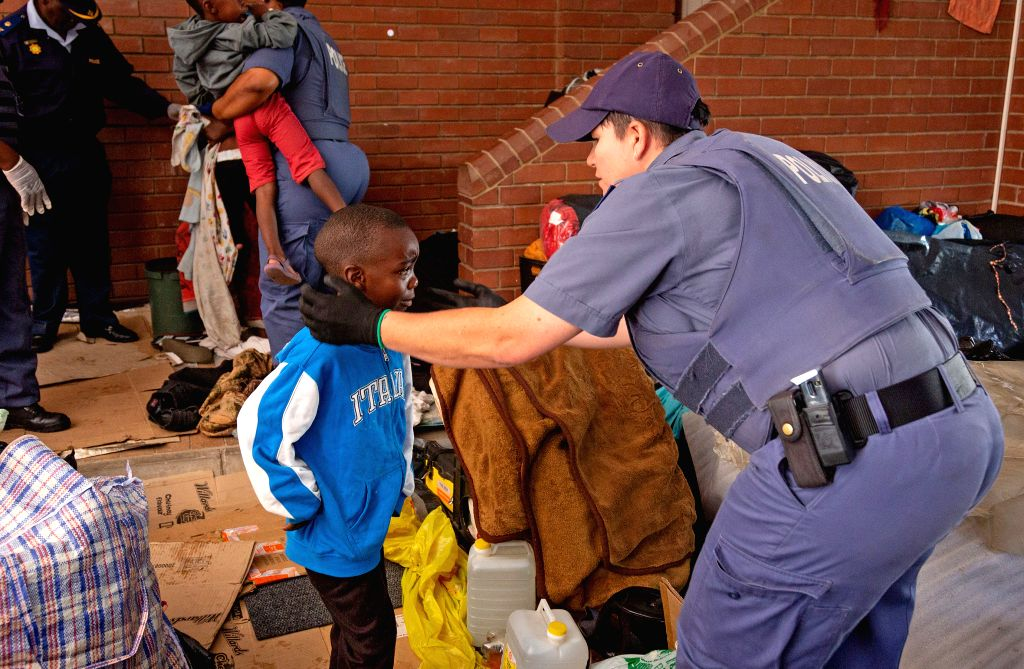 PRETORIA, Nov. 15, 2019 - A police officer helps a refugee child to remove from the United Nations High Commissioner for Refugees' offices in Pretoria, South Africa, on Nov. 15, 2019. South African ...