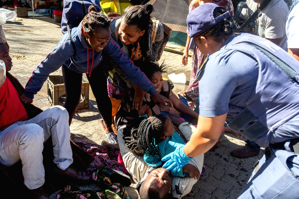 PRETORIA, Nov. 15, 2019 - Refugees cling to one another as they are arrested by police near the United Nations High Commissioner for Refugees' offices in Pretoria, South Africa, on Nov. 15, 2019. ...