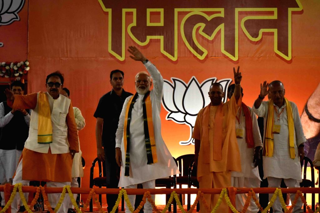 Prime Minister Narendra Modi accompanied by Uttar Pradesh Chief Minister Yogi Adityanath, state BJP President Mahendra Nath Pandey, waves to crowd during a party meeting, in Varanasi, on ... - Narendra Modi and Mahendra Nath Pandey