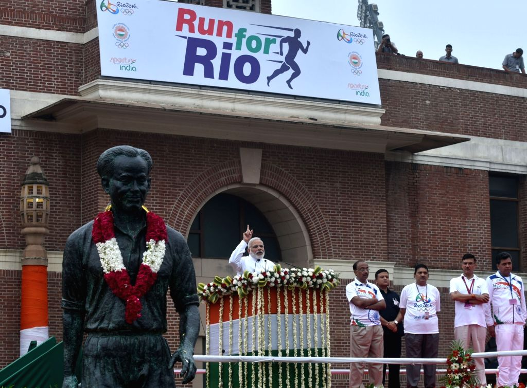 """Prime Minister Narendra Modi addressing at the flagging off ceremony of """"Run For Rio"""", at Major Dhyan Chand National Stadium, in New Delhi on July 31, 2016. Minister of State for ... - Narendra Modi and Rajiv Yadav"""
