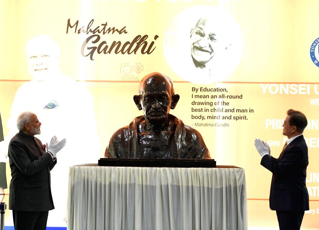 Prime Minister Narendra Modi and South Korean President Moon Jae-unveil the bust of Mahatma Gandhi at Yonsei University, in Seoul, South Korea on Feb 21, 2019. - Narendra Modi