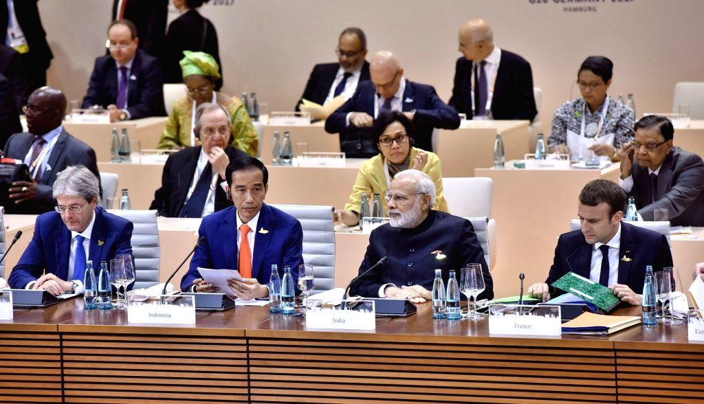 Prime Minister Narendra Modi at the Plenary Session of G-20 Nations in Hamburg, Germany on July 7, 2017. Also seen French President Emmanuel Macron and Indonesian President Joko Widodo. - Narendra Modi