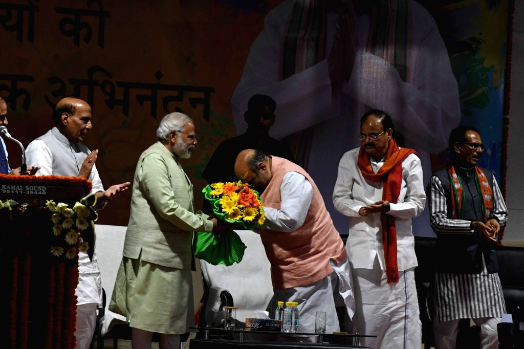 Prime Minister Narendra Modi being felicitated by BJP president Amit Shah and senior party leaders at BJP party office in New Delhi on March 12, 2017. - Narendra Modi and Amit Shah