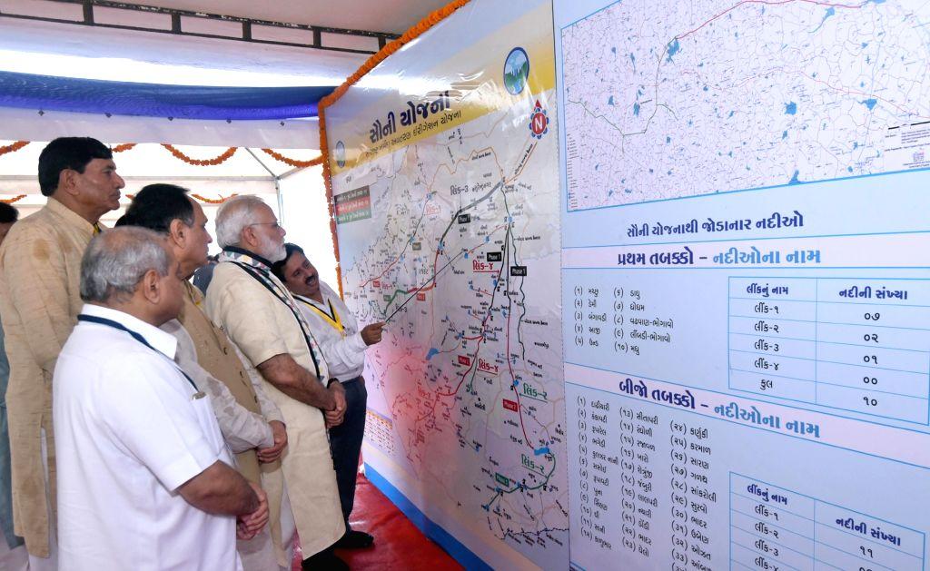 Prime Minister Narendra Modi being given a presentation on Aji-3 Dam under Phase-I of Saurashtra Narmada Avtaran Irrigation (SAUNI) Yojana in Rajkot on June 29, 2017. Also seen Gujarat Chief ... - Narendra Modi and Nitinbhai Patel