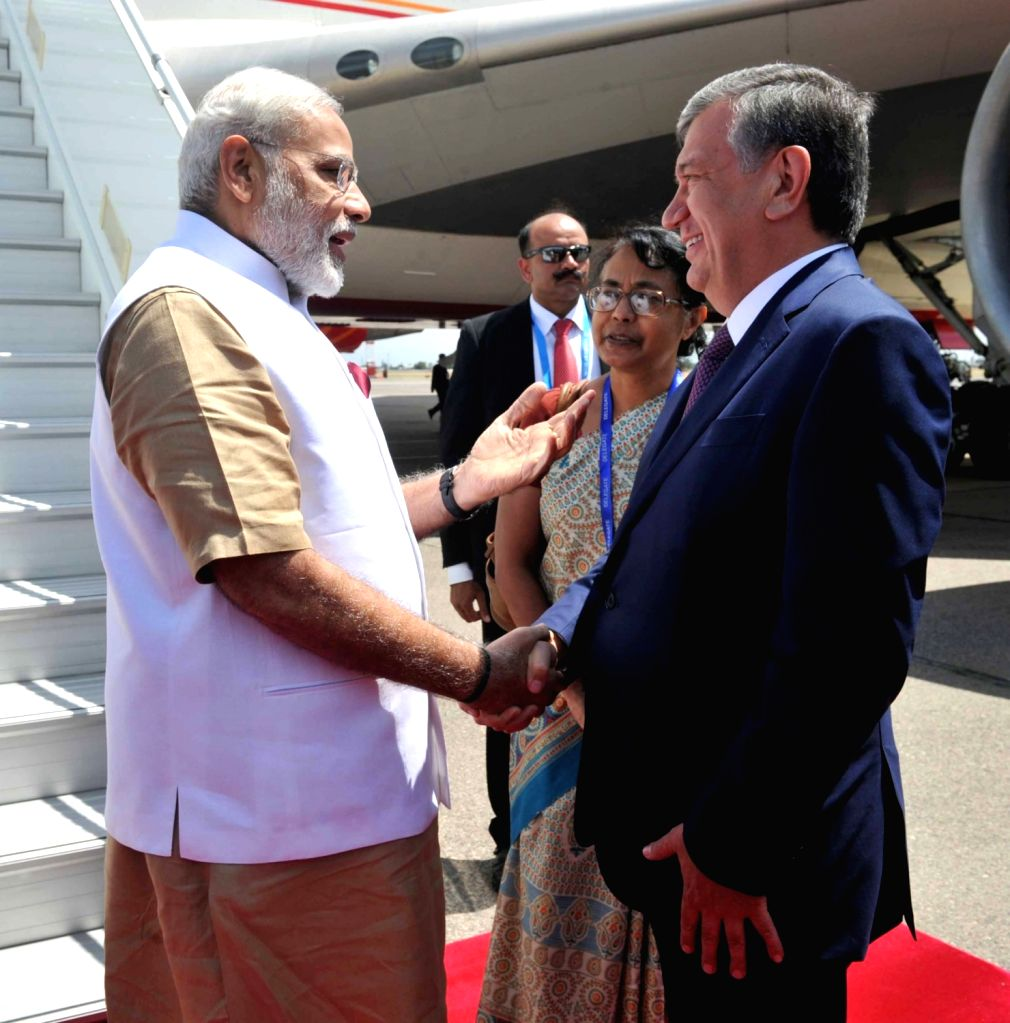 Prime Minister Narendra Modi being received by the Uzbek Prime Minister Shavkat Mirziyoev, on his arrival at Tashkent International Airport in Uzbekistan on June 23, 2016. - Narendra Modi