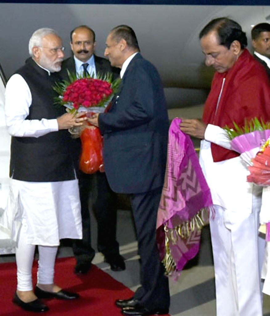 Prime Minister Narendra Modi being received by the Andhra Pradesh and Telangana Governor ESL Narasimhan and the Telangana Chief Minister K Chandrasekhar Rao on his arrival in Hyderabad on ... - Narendra Modi and K Chandrasekhar Rao