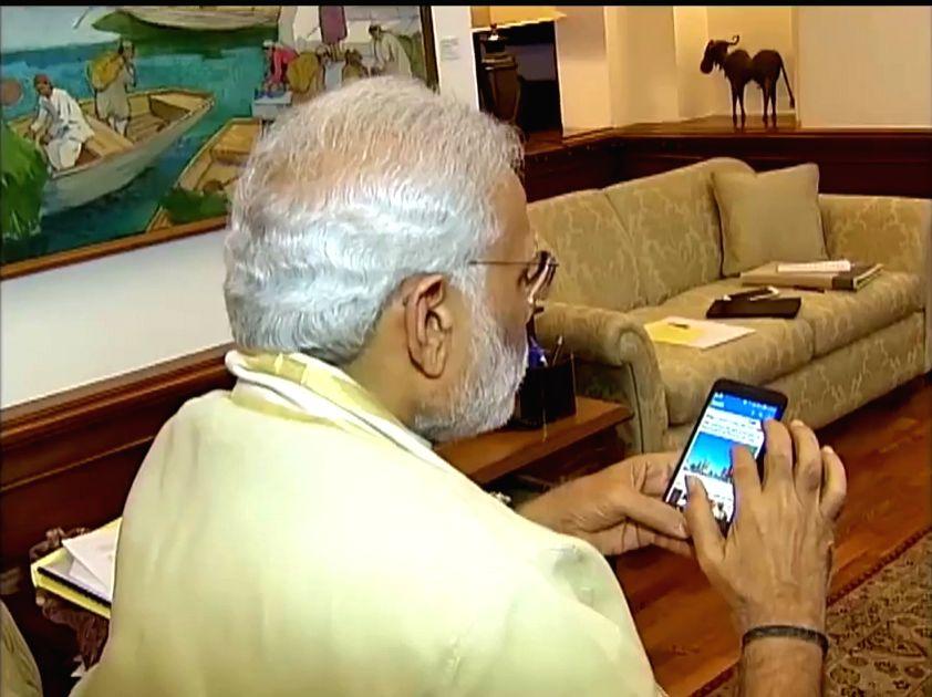 Prime Minister Narendra Modi busy working on his mobile phone. (Photo: IANS) - Narendra Modi