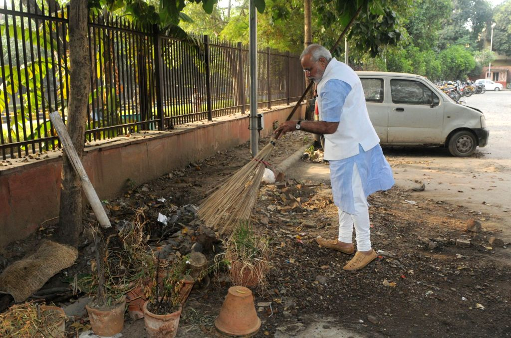 Prime Minister Narendra Modi cleans the premises of Mandir Marg Police Station during his surprise visit, in New Delhi, on Oct. 2, 2014. (Photo: IANS/PIB) - Narendra Modi
