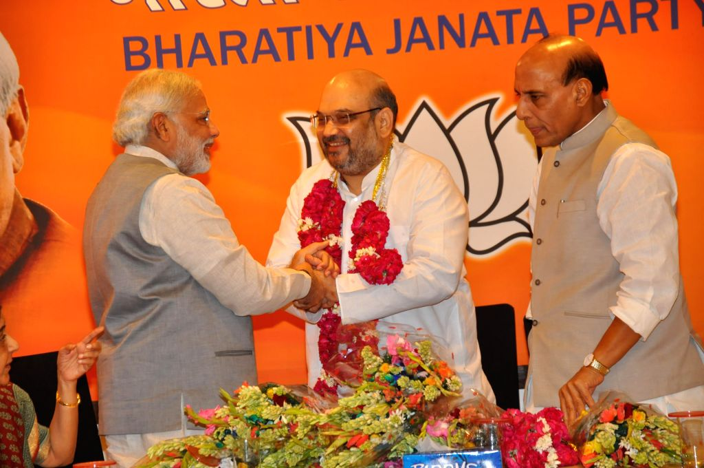 Prime Minister Narendra Modi congratulates new BJP chief Amit Shah on his elevation during a press conference  in New Delhi on July 9, 2014. Also seen Union Home Minister Rajnath Singh. - Narendra Modi and Rajnath Singh