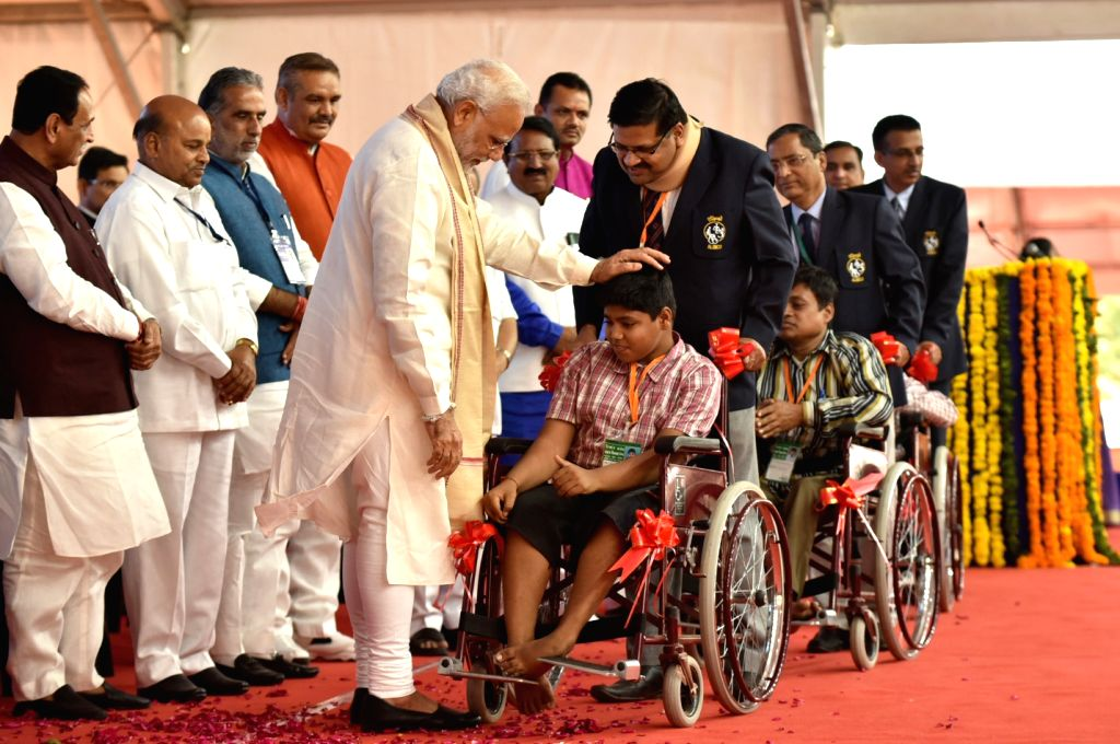 Prime Minister Narendra Modi distributes the aids and equipment at the Saamaajik Adhikaarita Shivir in Vadodara on Oct 22, 2016. Also seen Union Minister for Social Justice and Empowerment ... - Narendra Modi
