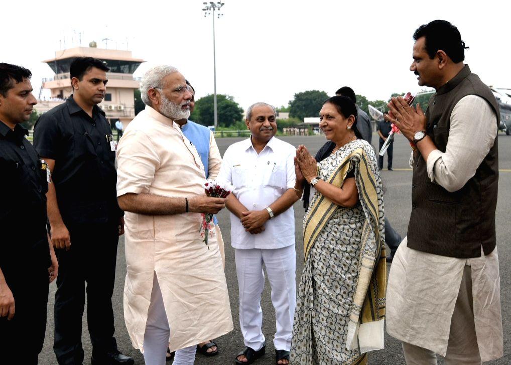 Prime Minister Narendra Modi embarks for his journey to Delhi from Bhavnagar after finishing his Gujarat tour on Sept 17, 2017. Also seen Gujarat Deputy Chief Minister Nitinbhai Patel. - Narendra Modi and Nitinbhai Patel