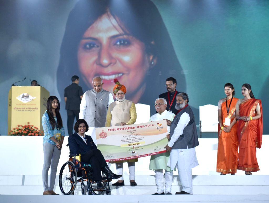 Prime Minister Narendra Modi felicitate Rio Paralympic Silver Medalist Deepa Malik with award of Rs.4 crore during Haryana Swarna Jayanti celebrations in Gurugram on Nov 1, 2016. Also seen ... - Narendra Modi, Malik, Kaptan Singh Solanki and Manohar Lal Khattar