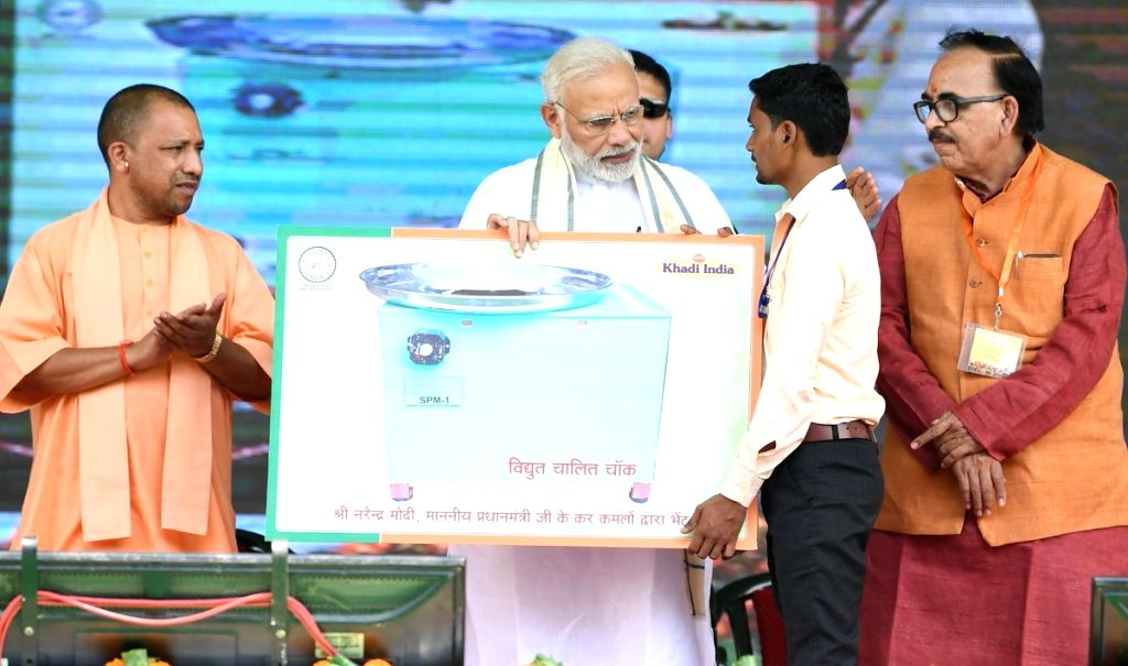Prime Minister Narendra Modi felicitates a beneficiary at the foundation stone laying ceremony of various development projects along with Uttar Pradesh Chief Minister Yogi Adityanath and UP ... - Narendra Modi and Mahendra Nath Pandey
