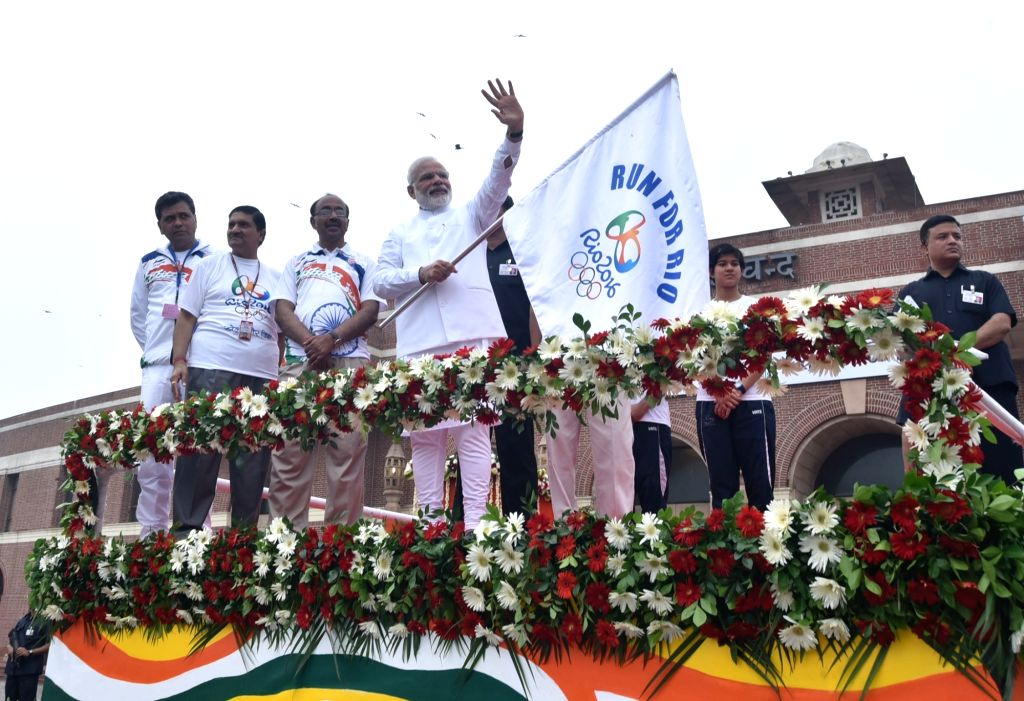 """Prime Minister Narendra Modi flagging off the """"Run For Rio"""", at Major Dhyan Chand National Stadium, in New Delhi on July 31, 2016. Minister of State for Youth Affairs and Sports ... - Narendra Modi and Rajiv Yadav"""