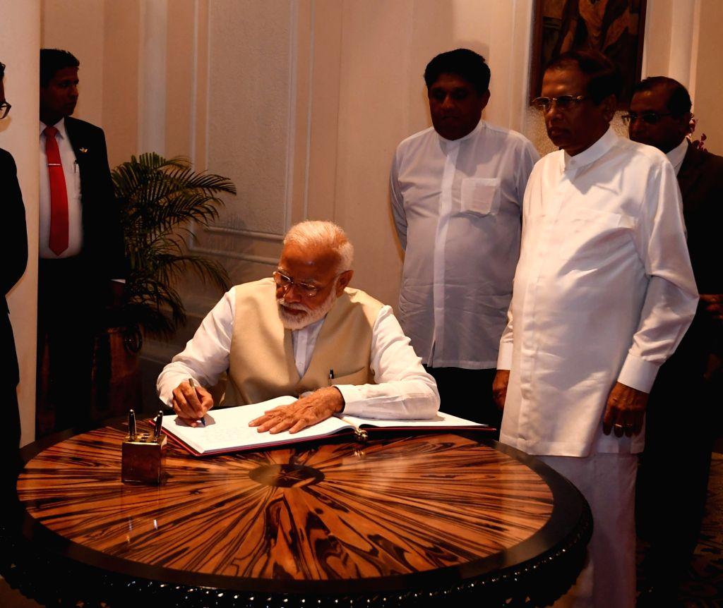 Prime Minister Narendra Modi in the presence of Sri Lanka President Maithripala Sirisena, signs the visitors book at President House in Colombo, Sri Lanka on June 9, 2019. - Narendra Modi