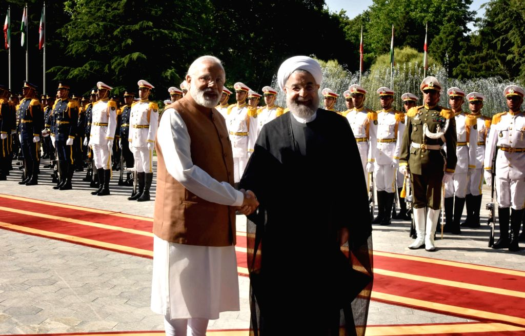 Prime Minister Narendra Modi inspecting the `Guard of Honour`, during his ceremonial welcome, at Saadabad Palace, in Tehran on May 23, 2016. The President of Iran Hassan Rouhani is also seen. - Narendra Modi and Hassan Rouhani