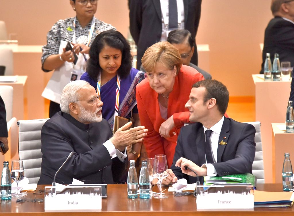 Prime Minister Narendra Modi interact with French President Emmanuel Macron and  German Chancellor Dr. Angela Merkel at the Plenary Session of G-20 Nations in Hamburg, Germany on July 7, ... - Narendra Modi
