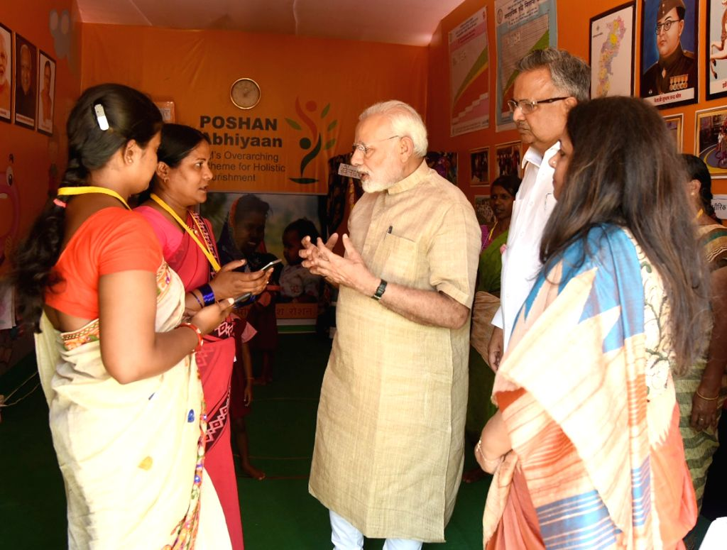 Prime Minister Narendra Modi interacts with Anganwadi workers and beneficiaries of Poshan Abhiyan in Chhattisgarh's Jangla, on April 14, 2018. Also seen Chhattisgarh Chief Minister Raman ... - Narendra Modi and Raman Singh