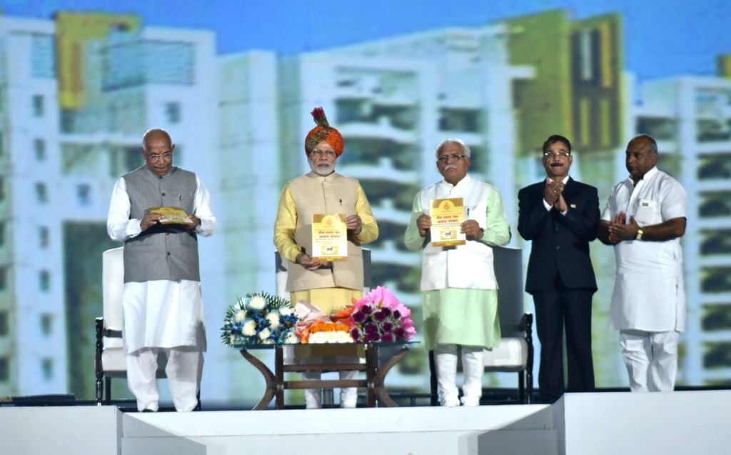 Prime Minister Narendra Modi launches the Deen Dayal Upadhyay Jan Awaas Yojana by releasing the brochure during Haryana Swarna Jayanti celebrations in Gurugram on Nov 1, 2016. Also seen ... - Narendra Modi, Kaptan Singh Solanki and Manohar Lal Khattar