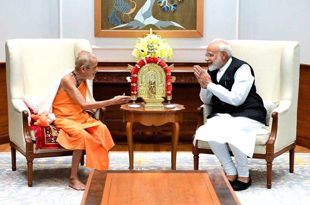 Prime Minister Narendra Modi meets Pejawar Adhokshaja Math seer Sri Vishwesha Theertha Swamiji, in New Delhi on July 16, 2019. - Narendra Modi