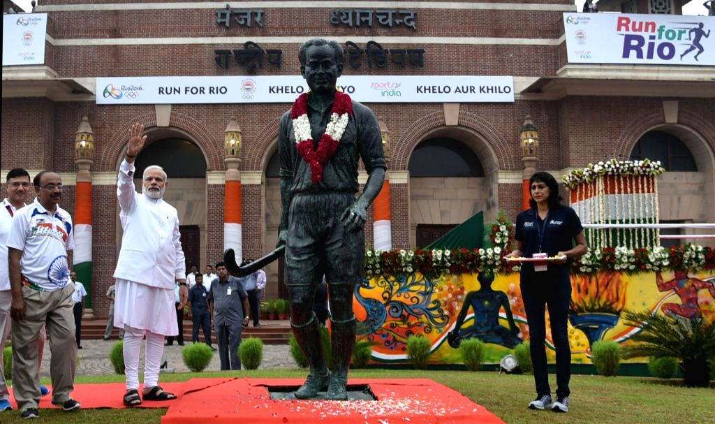 "Prime Minister Narendra Modi paying tributes to Major Dhyan Chand, at the flagging off ceremony of ""Run For Rio"", at Major Dhyan Chand National Stadium, in New Delhi on July 31, ... - Narendra Modi and Rajiv Yadav"