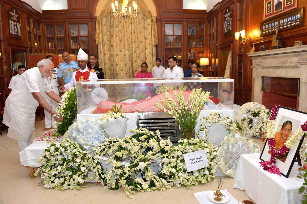 Prime Minister Narendra Modi pays tribute to the mortal remains of President Pranab Mukherjee's wife Suvra at Rashtrapati Bhawan on Aug 18, 2015. - Narendra Modi and Pranab Mukherjee