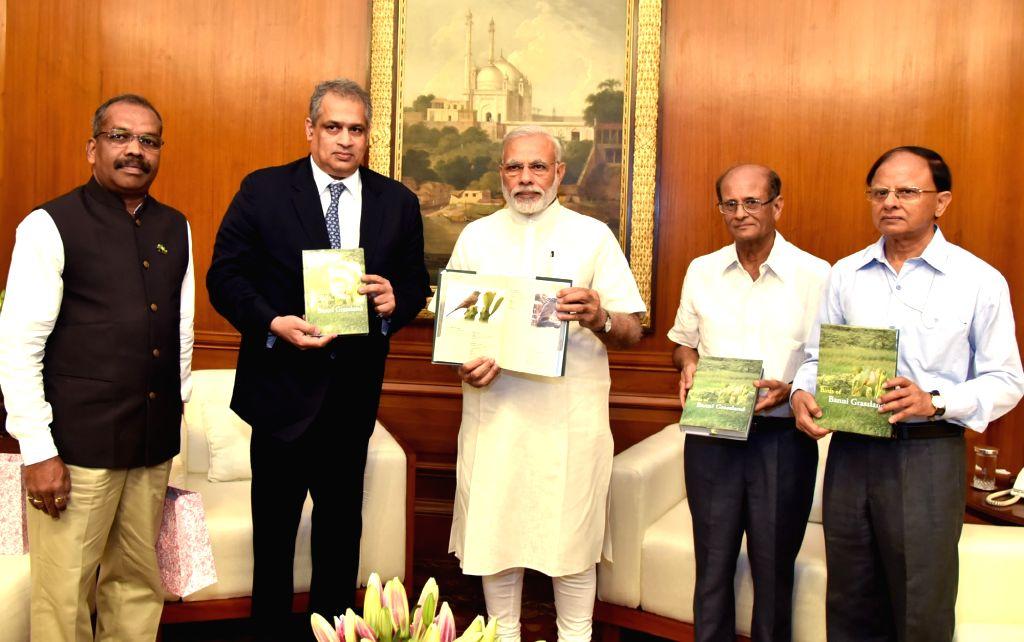 Prime Minister Narendra Modi releases `The Birds of Banni Grassland` - a book, presented by the Scientists of Gujarat Institute of Desert Ecology, in New Delhi on June 28, 2016. - Narendra Modi